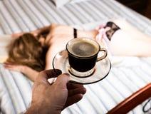 读一本厚实的书的美丽的妇女说谎在床,特写镜头咖啡杯 库存图片