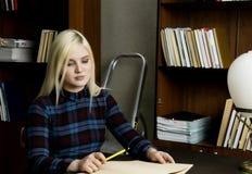 读一本大书的少妇在图书馆里 有书的书架 库存照片