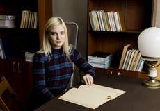 读一本大书的少妇在图书馆里 有书的书架 免版税库存照片