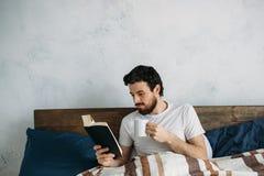 读一本大书的有胡子的人在他的卧室 库存照片