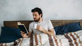 读一本大书的有胡子的人在他的卧室 免版税库存图片
