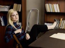 读一本大书的年轻女性图书管理员在图书馆里 有书、活梯和书桌的书架有灯的 库存图片