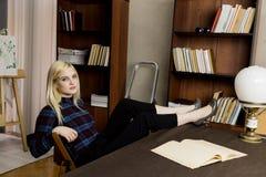 读一本大书的年轻女性图书管理员在图书馆里 有书、活梯和书桌的书架有灯的 库存照片