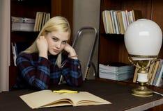 读一本大书的年轻女性图书管理员在图书馆里 有书、活梯和书桌的书架有灯的 图库摄影