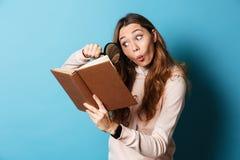 一本女孩阅读书的画象与放大镜的 库存照片