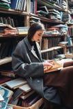 一本妇女阅读书的画象在一个老图书馆里 免版税库存图片