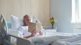 一本富有思想的年迈的人阅读书的移动式摄影车射击在医院 股票录像