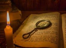 一本开放古老祈祷书和一个放大镜在它的开放页在一个蜡烛的光下 免版税库存图片