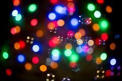 一本新年` s诗歌选和飞行肥皂泡的多彩多姿的被弄脏的光作为背景 免版税库存图片