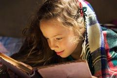 读一本旧书的逗人喜爱的学校女孩画象冷的天 免版税库存照片