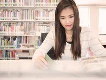 读一本杂志的一名美丽的亚裔妇女在图书馆里 免版税库存照片