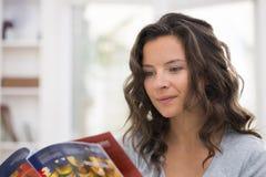 读一本杂志的俏丽的妇女在她的客厅 库存照片