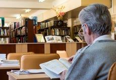 读一本杂志的年长人在图书馆的阅览室 库存图片