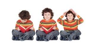 读一本红色书的三个相等的孩子供以座位 免版税图库摄影