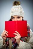 读一本红色书的腼腆的少妇 免版税库存照片