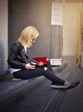 读一本红色书的行家女孩 库存图片