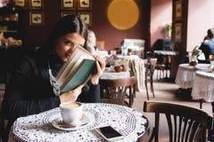 一本美丽的女孩阅读书的画象在咖啡馆的 饮料 免版税库存照片