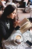 一本美丽的女孩阅读书的画象在咖啡馆的 饮料 免版税库存图片