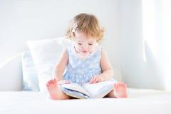一本蓝色礼服阅读书的滑稽的小孩女孩 免版税库存图片