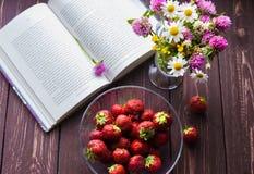 一本被打开的书、一个碗有新成熟开胃strawbwrries的和领域花束在黑暗的土气木头开花 图库摄影