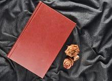 一朵书和干玫瑰在灰色织品背景 免版税库存照片