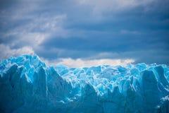 以一朵云彩为背景的参差不齐的蓝色冰川在天空 Shevelev 库存图片