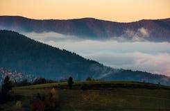 一朵云彩的上升在山的在黎明 免版税库存图片