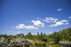 一朵云彩的看法在天空,岩石峭壁的在一个夏天,晴朗的d 免版税库存照片