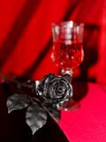 一朵人为黑色玫瑰和一杯与选择聚焦的酒 免版税库存图片