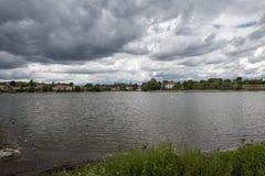 一朵大池塘和黑暗,恐怖的云彩的岸的一个小村庄在它上 库存照片