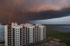 一朵巨大的雷云盖了房子 与彩虹的天空 免版税库存照片