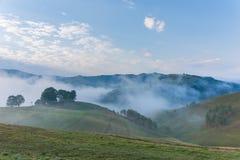一朵有雾的早晨的美好的山风景与和老房子、树和云彩 免版税库存图片