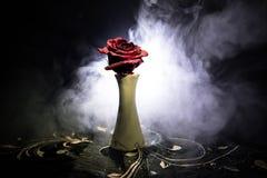 一朵枯萎的玫瑰符号化失去的爱,离婚,或者一个坏关系,死者在与烟的黑暗的背景上升了 免版税库存图片
