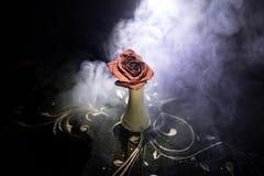 一朵枯萎的玫瑰符号化失去的爱,离婚,或者一个坏关系,死者在与烟的黑暗的背景上升了 免版税库存照片