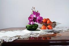 一朵桃红色兰花花的五颜六色的静物画在一个绿色花瓶的和 免版税库存图片