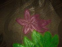 一朵桃红色花的图象与绿色的在织品纹理的棕色背景离开 免版税库存照片