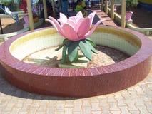一朵桃红色颜色莲花的科摩林角,泰米尔纳德邦,印度- 2008 10月7日,五颜六色的石雕象与绿色叶子的 库存照片