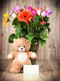 一朵玩具熊和明亮的花在花瓶 库存照片