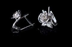 以一朵玫瑰的形式银色耳环在一黑backgr 库存照片