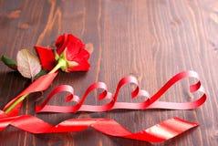 一朵玫瑰的心脏与丝带的 库存照片