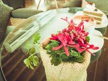 一朵红色兰花用热的上等咖啡咖啡和上等咖啡在舒适咖啡桌结块 库存照片