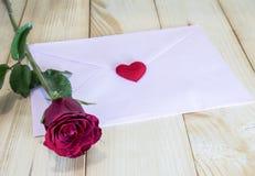 一朵红色玫瑰和桃红色信封4 库存照片