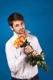 给一朵红色玫瑰的年轻人 免版税库存照片