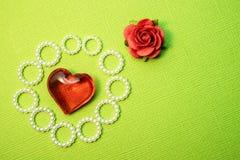 一朵红色花和一红色心脏在一个绿色基体,工艺从纸和首饰 库存图片