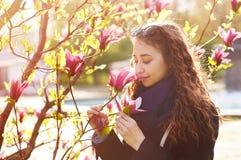 一朵美丽的妇女嗅到的木兰花的春天画象 库存照片