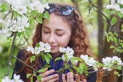 一朵美丽的妇女嗅到的木兰花的春天画象 库存图片