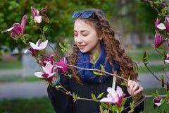 一朵美丽的妇女嗅到的木兰花的春天画象 免版税库存图片