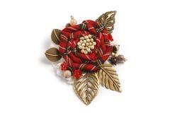 以一朵花的形式手工制造别针从与金属的一种红色方格的织品离开 免版税库存照片
