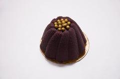 以一朵花的形式紫色点心与在上面的金黄珍珠 库存照片