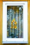 一朵黄色兰花在一个老木房子的窗口里 免版税库存图片